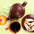 Top view of cup of tea and teapot on green tablecloths -  