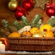 Christmas composition in basket with oranges and fir tree, on wooden background — Stock Photo #14949485
