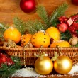 Christmas composition in basket with oranges and fir tree, on wooden background — Stock Photo #14949493