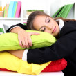 Royalty-Free Stock Photo: Tired business woman with pillows sitting at the table and sleeps