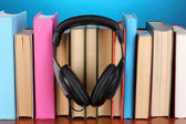 Headphones on books on wooden table on blue background — Stock Photo