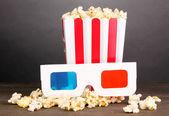 Popcorn och film glasögon på träbord på grå bakgrund — Stockfoto