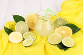 Citrus lemonade in glass pitcher of citrus around on yellow fabric on white wooden table close-up — Stock Photo