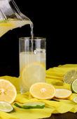 цитрусовые лимонад в стекла и кувшин цитрусовых вокруг на желтой ткани на деревянный стол крупным планом — Стоковое фото