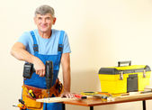 Builder drills board on table on wall background — Stock Photo