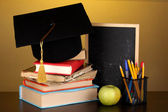 Books and magister cap against school board on wooden table on yellow background — Stock Photo