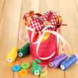 Royalty-Free Stock Photo: Color bucket with multicolor ribbons and thread on wooden background