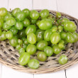 Ripe green grapes close-up on wicker cradle on wooden table - Stock Photo