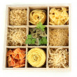 Nine types of pasta in wooden box sections close-up isolated on white - Foto Stock