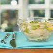 Salad of squid rings, lemon and lettuce in a glass bowl on wooden table close-up — Stock Photo #14954467