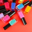 Group of bright nail polishes, on red background — Stock Photo #14955409