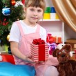 Little girl sits near a Christmas tree with gift in hand in festively decorated room — Stock Photo #14955987