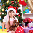Little girl in Santa hat near the Christmas tree in festively decorated room — Stock Photo #14956005