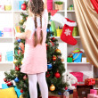 Royalty-Free Stock Photo: Little girl decorates  Christmas tree in festively decorated room
