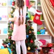 Little girl decorates Christmas tree in festively decorated room — Stock Photo #14956015