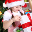 Stock Photo: Little girl opens gift in festively decorated room