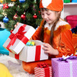 Little girl in suit of squirrels opens gift in festively decorated room — Stock Photo #14956029
