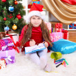 Beautiful little girl in red dress writes letter to Santa Claus in festively decorated room — Stock Photo #14956031