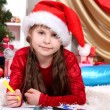 Beautiful little girl writes letter to Santa Claus in festively decorated room — Stock Photo #14956045