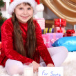 Beautiful little girl with milk and cookies for Santa Claus in festively decorated room — Stock Photo #14956049