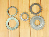 Metal cogwheels on wooden background — Stock Photo