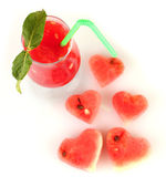 A glass of fresh watermelon juice and hearts of watermelon on white background close-up — Stock Photo