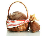 Tasty rye breads with ears in basket, isolated on white — Stock Photo