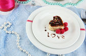 Plate with dessert in form of heart on celebratory table in honor of Valentine's Day close-up — Photo