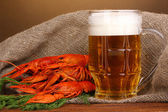 Tasty boiled crayfishes and beer on table on brown background — Stock Photo