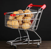 Ripe potatoes in trolley on wooden table on black background — Stock Photo