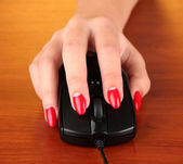 Closeup of female fingers and nails on computer mouse on wooden background — Foto de Stock