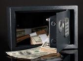 Money in open safe isolated on black — Stock Photo