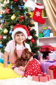 圣诞老人帽子圣诞节树在欢乐地装饰的屋子附近的小女孩 — 图库照片