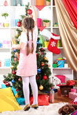Little girl decorates Christmas tree in festively decorated room — 图库照片