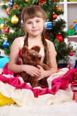 Beautiful little girl in holiday dress with toy in hands in festively decorated room — Stock Photo