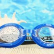 Blue swim goggles with drops on a bamboo pad, on blue sea background - Stock Photo