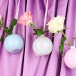 Beautiful roses in vases hanging on cloth background — Stock fotografie