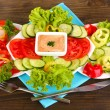 Chopped vegetables and sauce on plate on wooden table — Stock Photo