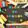Small chalkboard with school supplies on wooden background. Back to School - Stock Photo