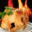 Roasted whole chicken on a white plate on wooden background close-up — Stock Photo
