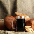 Tankard of kvass and rye breads with ears, on burlap background — Stock Photo #15313771