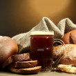 Tankard of kvass and rye breads with ears, on wooden table on brown background — Stock Photo #15313777
