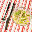 Salad of squid rings, lemon and lettuce in a glass bowl on striped tablecloth close-up — Stock Photo #15313847