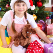 Little girl in Santa hat near the Christmas tree in festively decorated room — Stock Photo #15315693