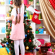 Little girl decorates Christmas tree in festively decorated room — Stock Photo #15315697