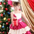 Royalty-Free Stock Photo: Beautiful little girl in holiday dress with gift in their hands in festively decorated room
