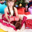 Stock Photo: Beautiful little girl in holiday dress with gift in hands in festively decorated room