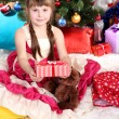 Beautiful little girl in holiday dress with gift in hands in festively decorated room — Stock Photo