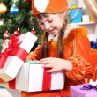 Little girl in suit of squirrels opens gift in festively decorated room — Stock Photo #15315735