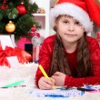 Royalty-Free Stock Photo: Beautiful little girl writes letter to Santa Claus in festively decorated room